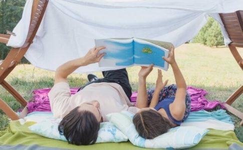 寝転がって本を読む親子