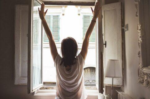 窓際でストレッチをする女性